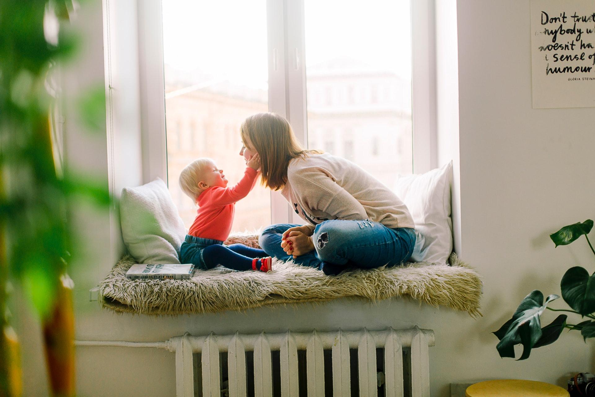 Imagem mostra bebê com as mãos na cara da mãe enquanto estão sentados perto da janela