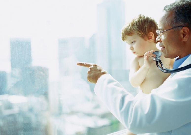Imagem mostra criança no colo do médico segurando um estetoscópio e olhando pela janela