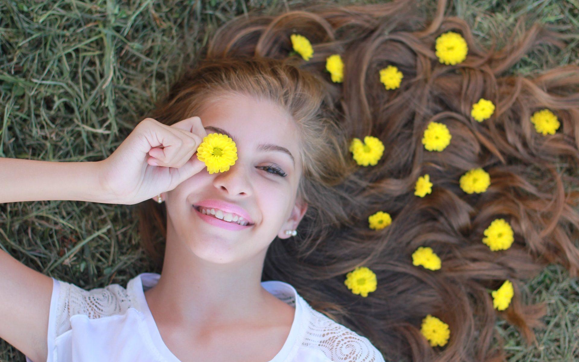 Banner mostra mulher deitada na grama com flores amarelas sobre seu cabelo