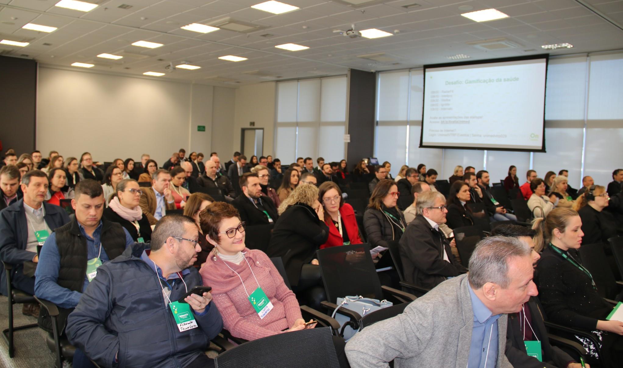 Imagem mostra pessoas assistindo o projeto Innovation Unimed