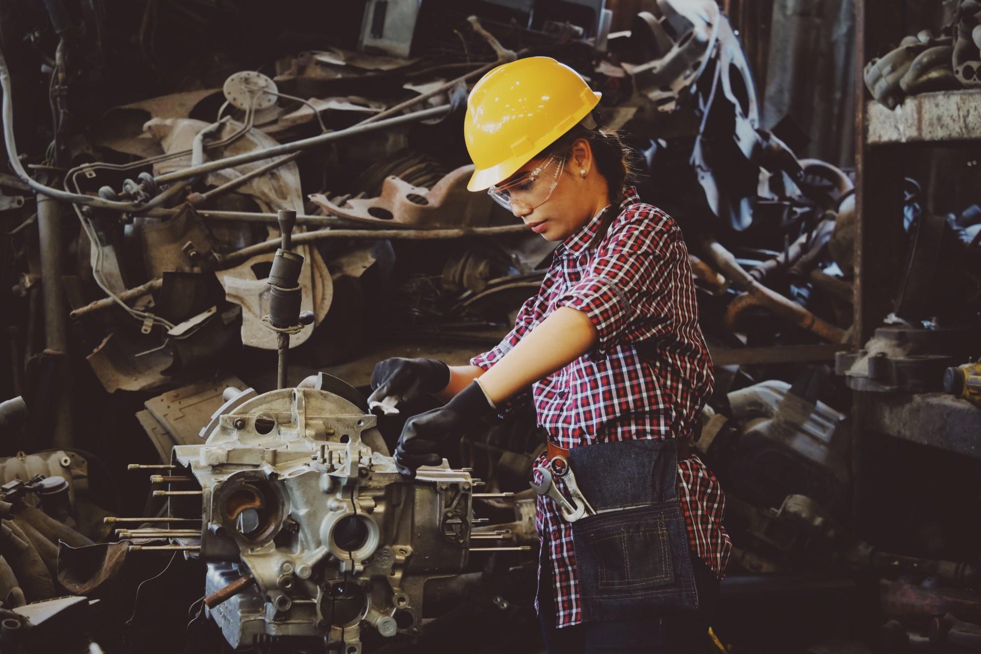 Imagem mostra mulher trabalhando em um motor utilizando EPIs