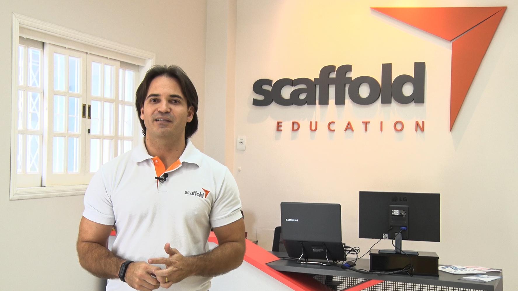Representante da startup Scaffold Education está de pé, ao lado do logotipo da empresa, que está aplicado em uma parede