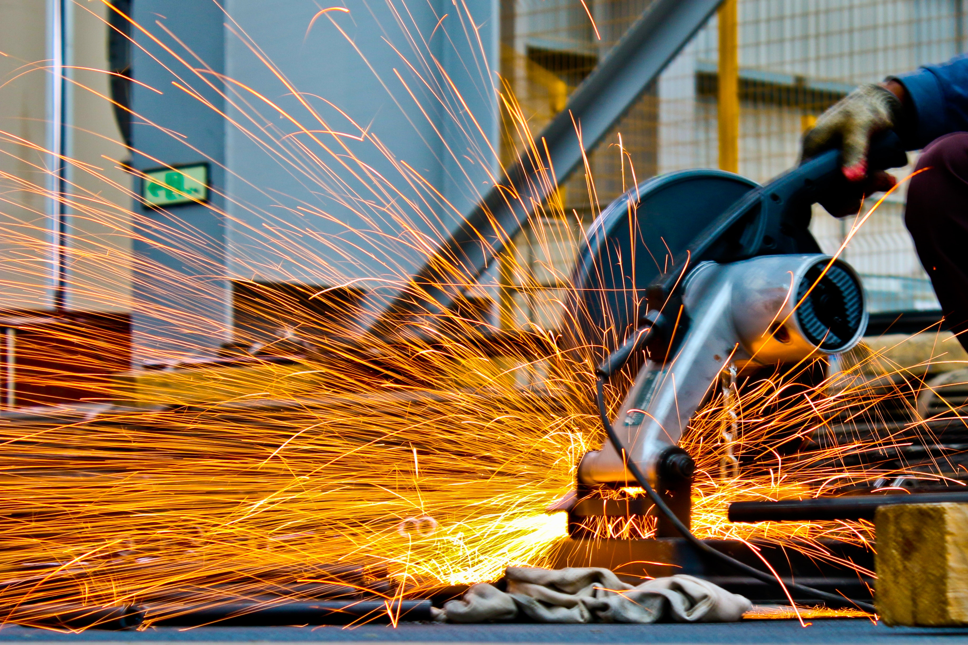 Pessoa utiliza serra circular para cortar ferros em uma obra