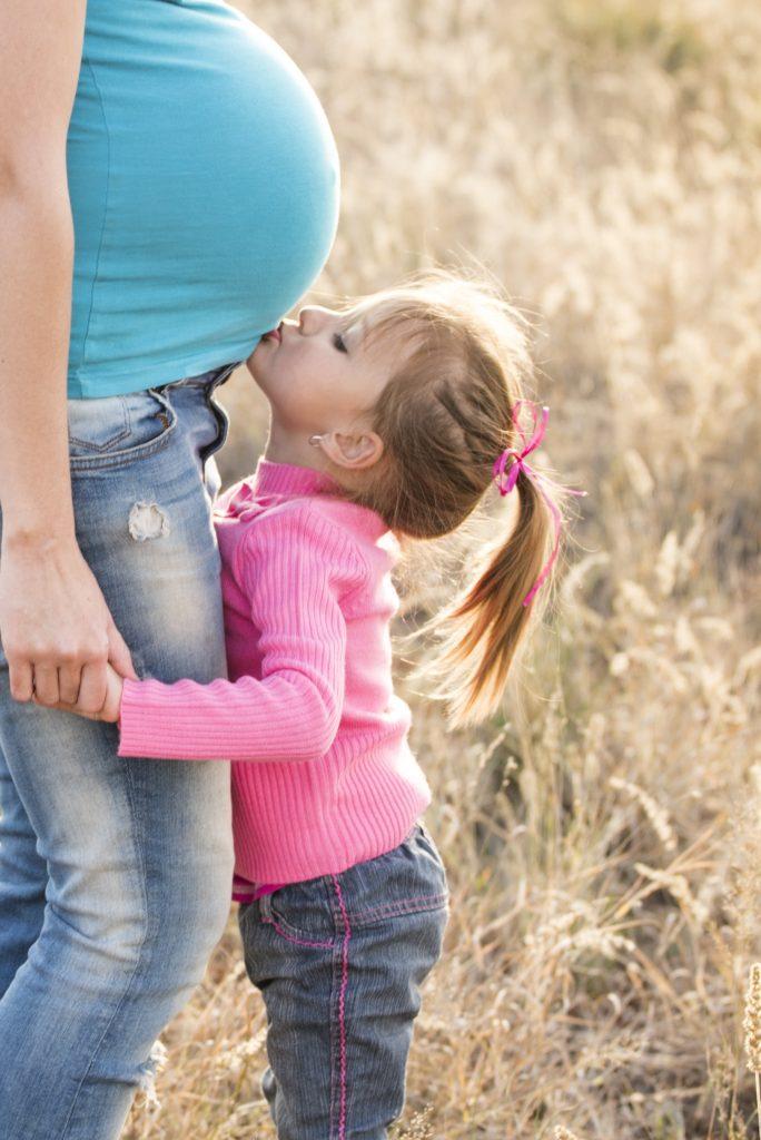 Menina pequena beija a barriga de uma mulher grávida