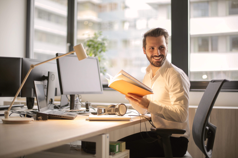 Homem sorridente segura agenda sentado em um escritório