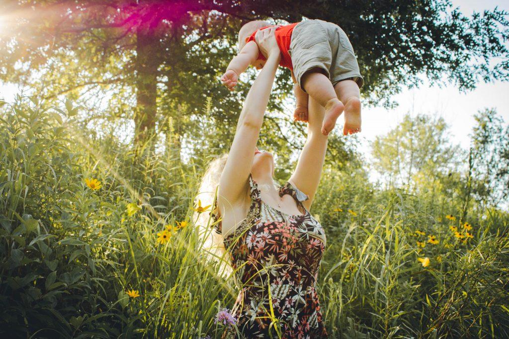 Mãe ergue criança pequena bem alto, em um local ao ar livre, com árvores e arbustos