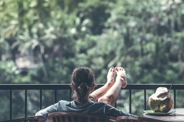 mulher de costas, sentada na varanda de casa, com os pés para o alto