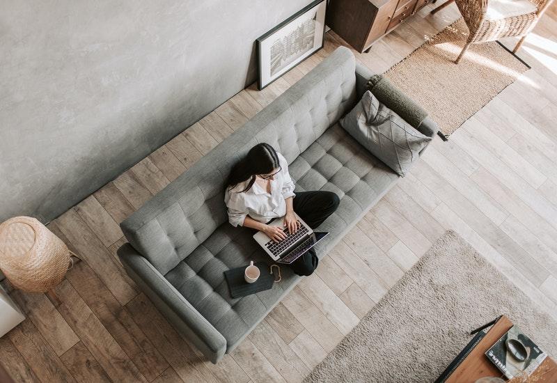 Imagem mostra mulher sentada no sofá mexendo no computador