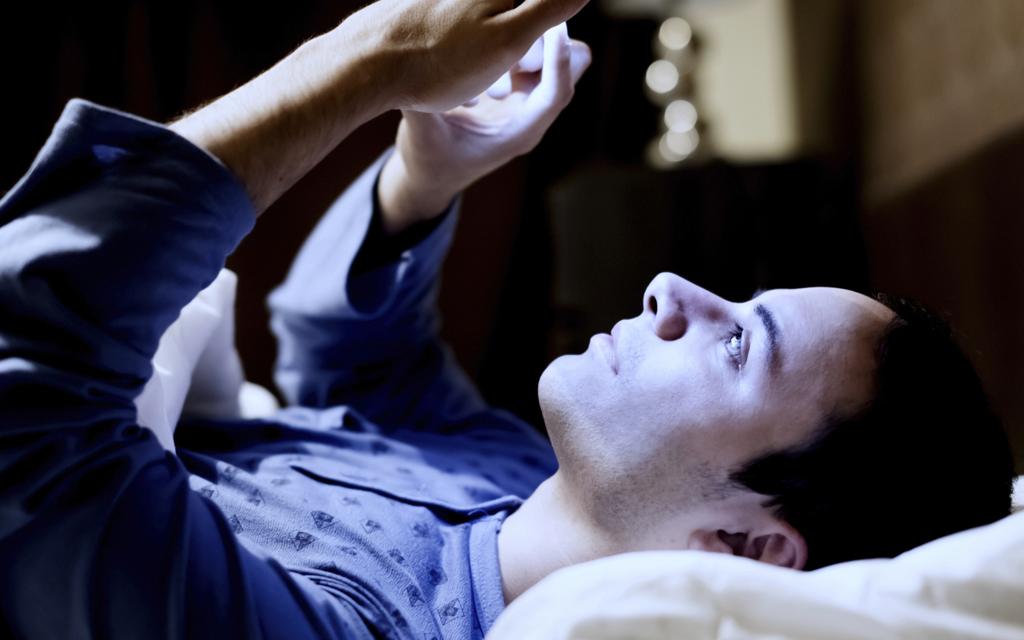 Rapaz deitado na cama mexendo no celular