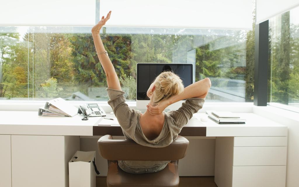 Mulher sentada em frente ao computador se alongando