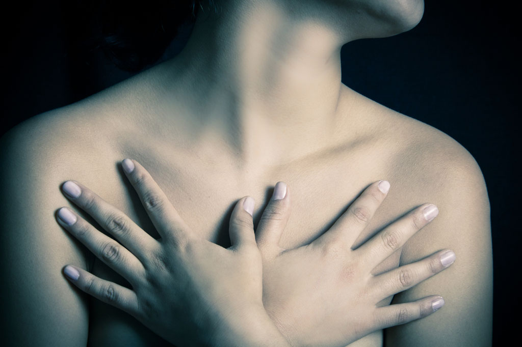 Mulher com as mãos cruzadas sobre o peito