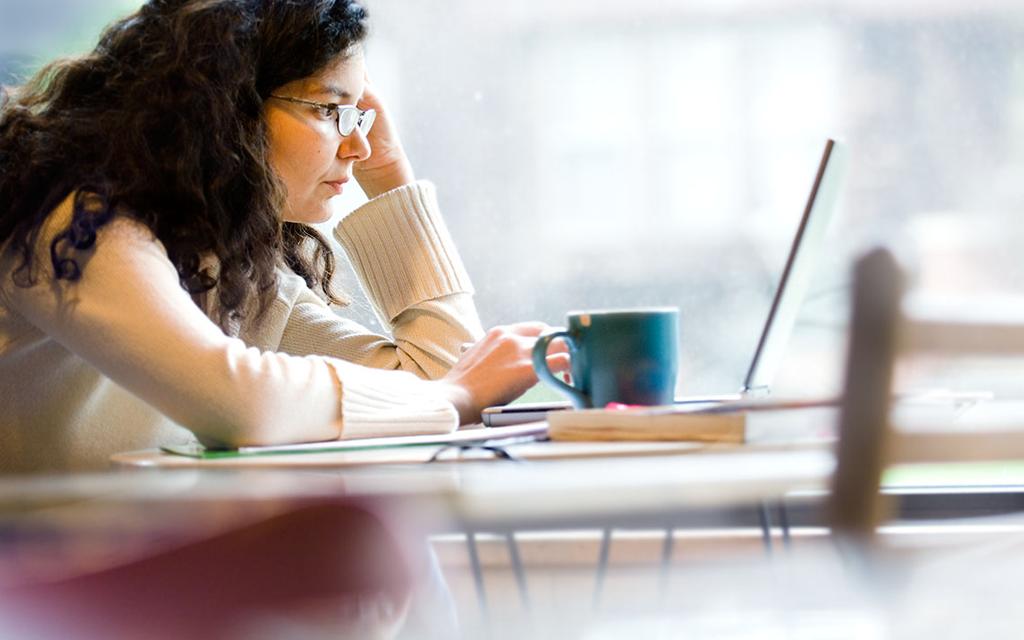 Mulher sentada em frente a um computador com feições de preocupação