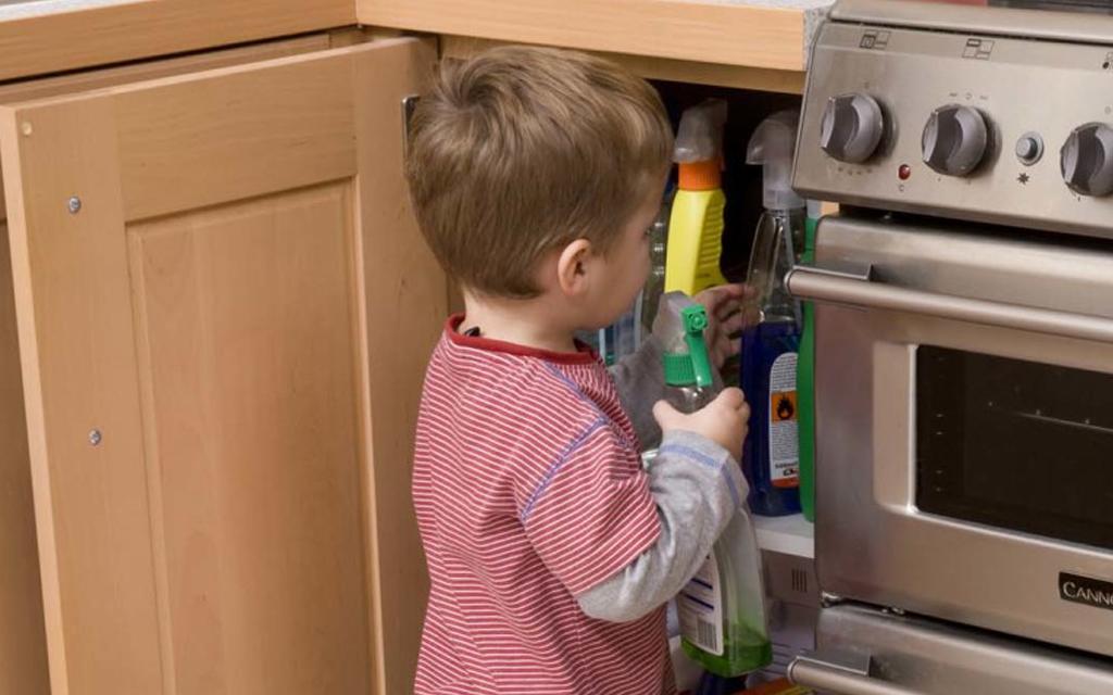 Criança brincando no armário com produtos de limpeza